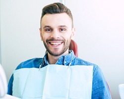 Happy male dental patient in blue shirt smiling after treatment