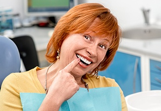 Older woman in dental chair pointing to smile