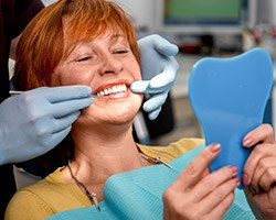 Senior woman in dental chair looking at her smile in the mirror