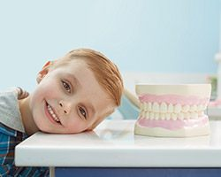 Smiling child next tooth model