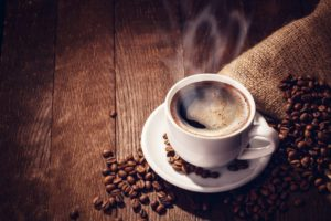 Steaming mug of hot coffee on a wooden table