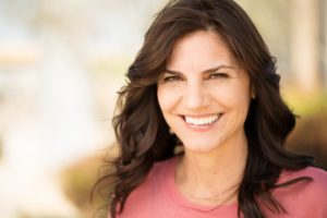Woman with dental implants smiling outside